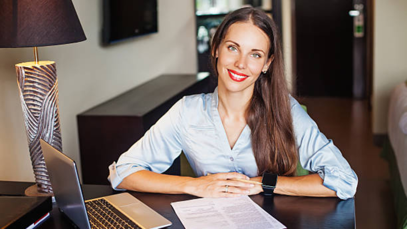 Beautiful business woman in casual dress sitting at a table with laptop looking at camera and smiling